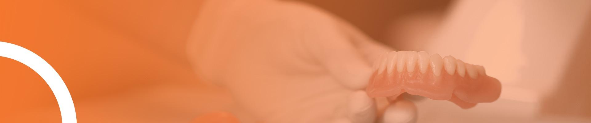 Zahnärztin hält Prothese in der Hand